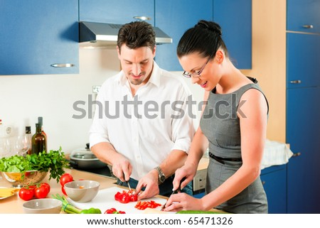 Young couple cooking - man and woman in their kitchen at home preparing vegetables for salad and pasta sauce - stock photo