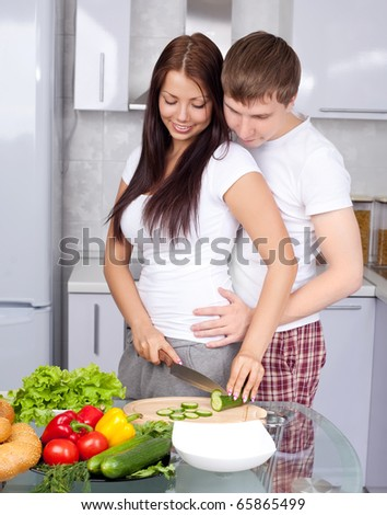 young couple cooking together in the kitchen at home - stock photo
