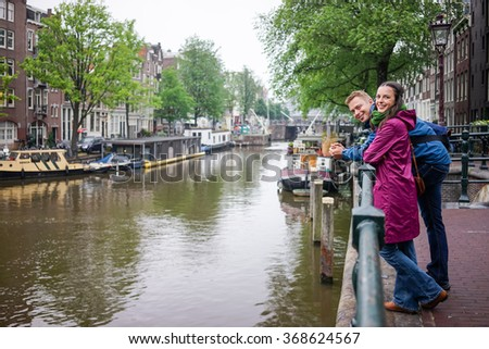 Young couple Cucazian enjoy the beauty of Amsterdam, even if it rains - stock photo