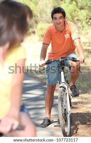 Young couple cycling in the forest - stock photo