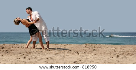 Young couple dancing on the beach - stock photo