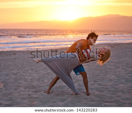 Young couple dancing on the Beach at Sunset - stock photo