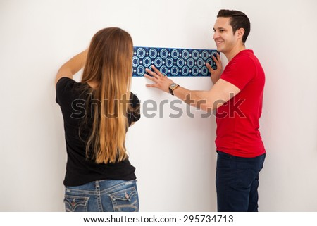Young couple decorating and pasting a wallpaper in a wall in their new home - stock photo