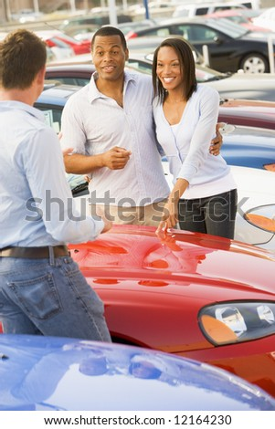 Young couple discussing new car with salesman on lot - stock photo