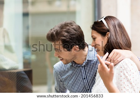 Young couple discussing something in a store as they stand arm in arm looking through the window at the merchandise - stock photo