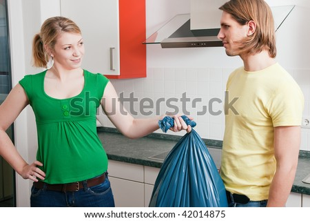 Young couple doing chores and cleaning the apartment, he is not too happy to have to get out the garbage weaseling out of the task - stock photo