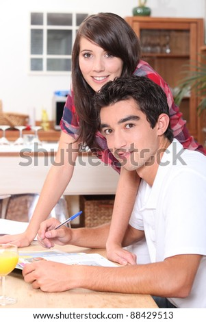Young couple doing paperwork at the kitchen table - stock photo