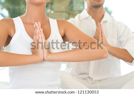 Young Couple Doing Yoga And Meditating, Closeup Shot - stock photo