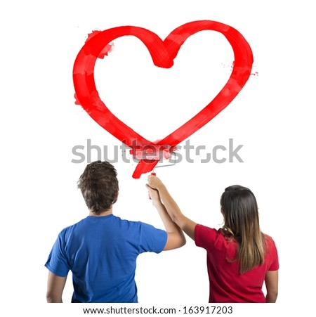 Young couple drawing a big red heart - stock photo
