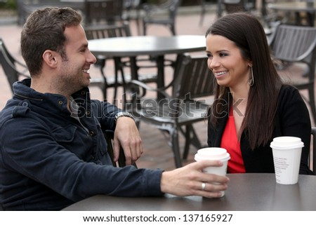 Young couple drinking coffee outside - stock photo