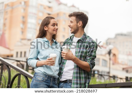 Young couple drinking coffee outside. Portrait of happy partners having break outside at summer  - stock photo