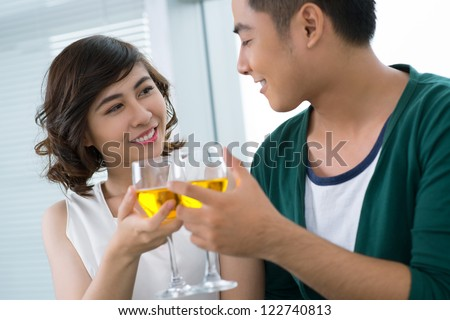 Young couple drinking to their love - stock photo