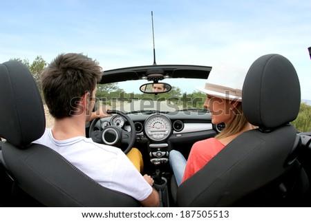 Young couple driving convertible car - stock photo