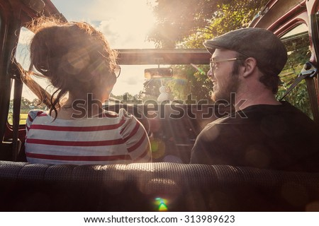 Young couple, driving in an old, convertible, classic car, driving towards the setting afternoon sun - stock photo