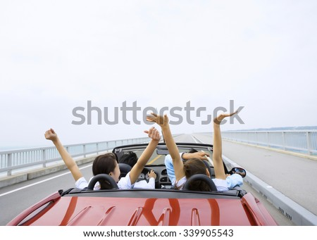 Young Couple Driving In Open Top Car - stock photo