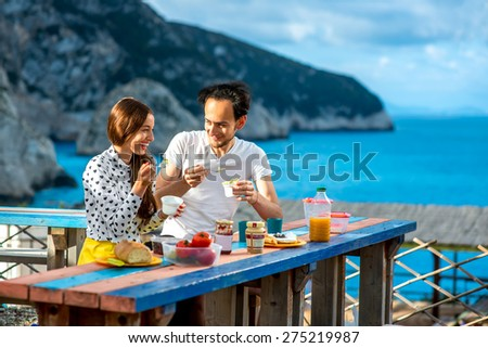 Young couple eating breakfast on the table near the sea on their summer vacation - stock photo