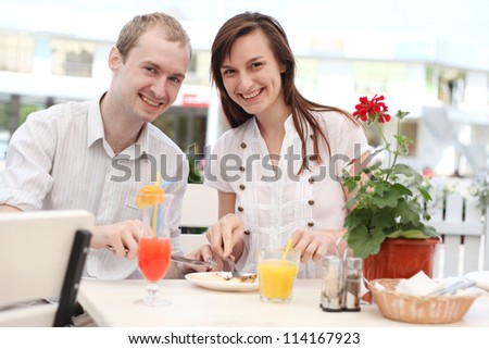 Young couple eating pizza in cafe - stock photo