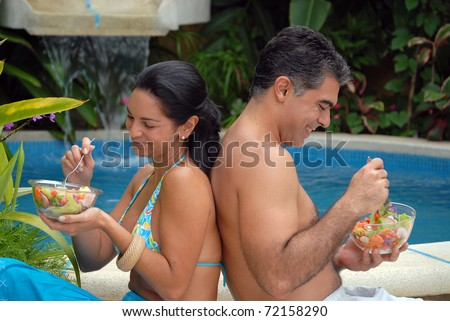 Young couple eating salad behind a swimming pool. - stock photo