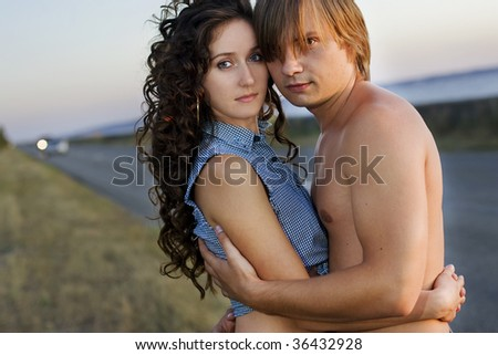 Young couple embrace at the edge of a nice road near the sea. - stock photo