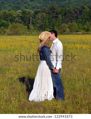 Young couple embrace in a field of yellow flowers.  Holding hands they kiss.  She is wearing a cowboy hat and denim jacket.  He is wearing jeans and white shirt. - stock photo
