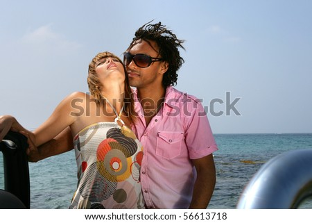 Young couple embraced in front of the sea - stock photo
