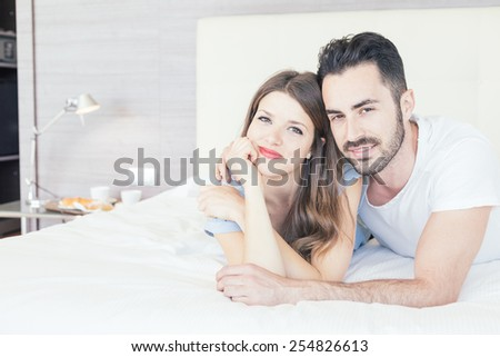 Young couple embraced on the bed. They are in a modern hotel room and they wear underwear. They embrace each other and look at camera. Love and lifestyle concepts. - stock photo