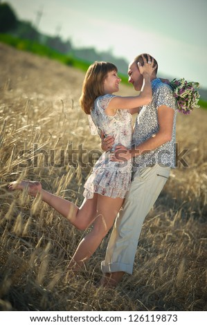 young couple embracing in a field of rye - stock photo