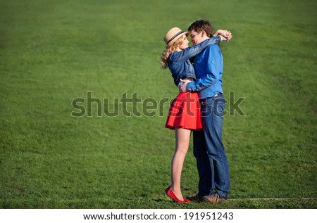 young couple embracing on a green lawn - stock photo