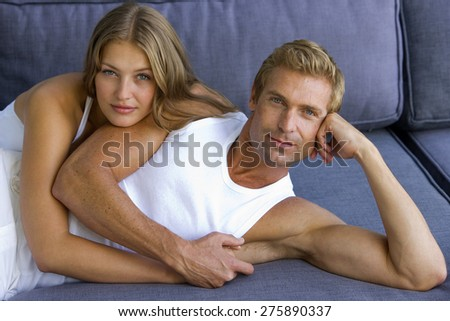 Young couple embracing on blue sofa. - stock photo