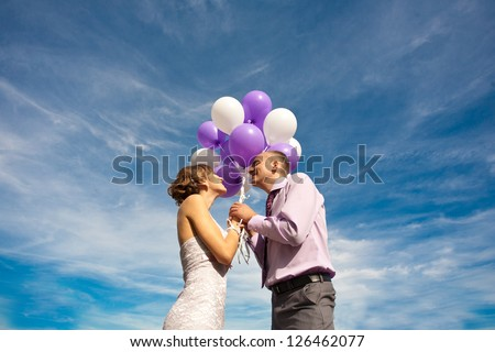Young couple embracing over sky and holding bunch of baloons - stock photo