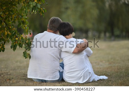 Young couple embracing sitting beside the road - stock photo