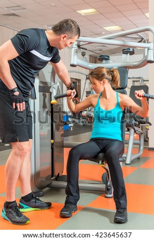 young couple engaged in the gym together - stock photo