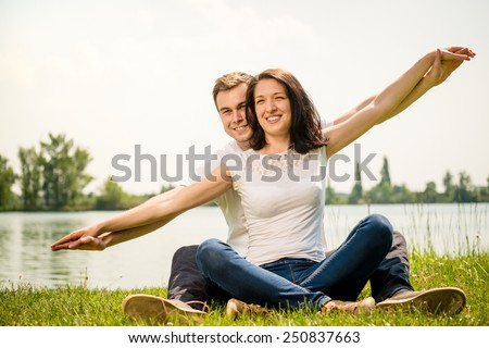 Young couple enjoy life together in nature - making airplane with hands - stock photo