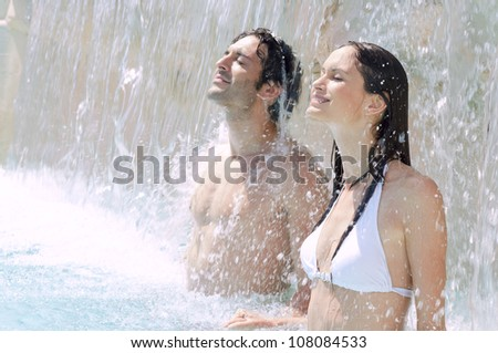 Young couple enjoy together waterfall freshness in a swimmingpool - stock photo