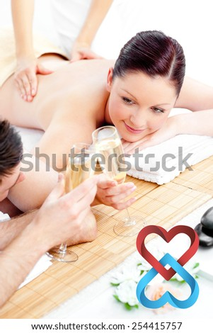 Young couple enjoying a back massage and drinking champagne against linking hearts - stock photo