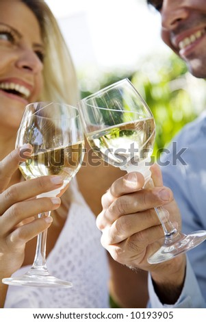 young couple enjoying a glass of white wine in the garden - stock photo