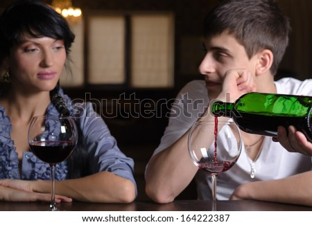 Young couple enjoying a glass of wine together at the bar in a nightclub with a male hand pouring wine from the bottle in the foreground - stock photo