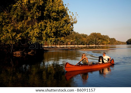 Young couple enjoying a trip in a canoe - sunset light - stock photo