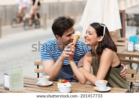 Young couple enjoying coffee at a street cafe laughing as they share an ice cream cone in the hot summer sun - stock photo