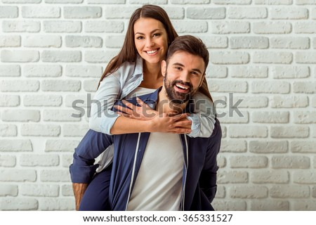 Young Couple Enjoying Piggyback Ride, against the background of a brick wall - stock photo