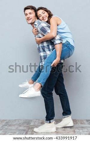 Young couple enjoying piggyback ride isolated on gray background - stock photo
