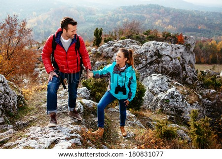 Young couple enjoying the moment on the rocks - stock photo