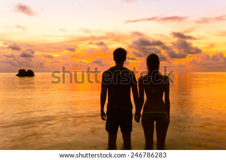 Young couple enjoying the sunset at the beach - stock photo