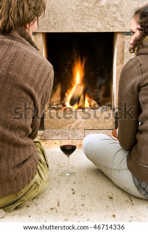 Young couple enjoying the warmth of a fire with a glass of wine - stock photo