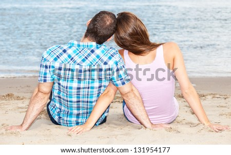 Young couple enjoys time at the beach - stock photo