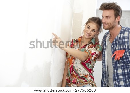 Young couple examining painting in new home under construction. - stock photo