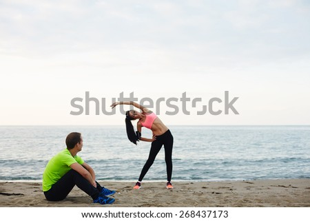 Young couple exercising and enjoying time outdoors, young fitness woman doing physical stretch exercise while her boyfriend taking break, couple working out on the beach at evening time - stock photo