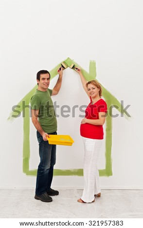 Young couple expecting a baby - preparing the child room in their new home - stock photo
