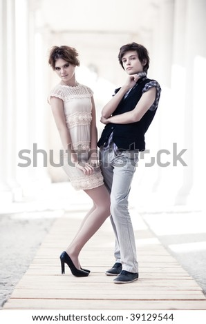 Young couple fashion. On bright white outdoors background. - stock photo