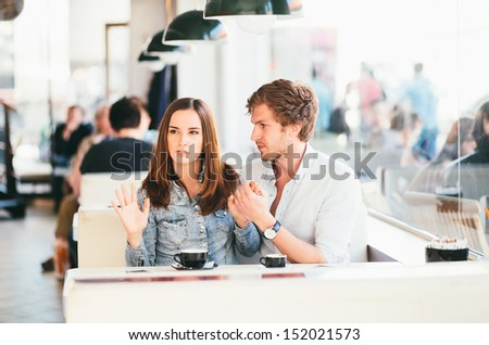 Young couple fighting in cafe - stock photo